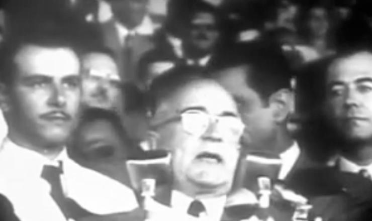 """Em trecho do documentário """"Getúlio Vargas"""" (1974), de Ana Carolina, Getúlio faz seu discurso no costumeiro evento de 1º de Maio, no estádio do Vasco da Gama, o primeiro do novo mandato.   Trabalhadores do Brasil    Depois de quase seisanos de afastamento, durante os quais nunca me saíram do pensamento a imagem e a lembrança do grato e longo convívio que mantive convosco, eis-me outra vez aqui ao vosso lado, para falar com a familiaridade amiga de outros tempos, epara dizer que voltei a fim de defender os interesses mais legítimos do povo, e promover as medidas indispensáveis ao bem-estar dos trabalhadores.  […]"""