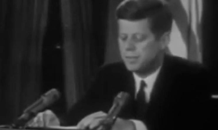 """Em pronunciamento nas redes de televisão, J. F. Kennedy revela ao mundo que a URSS instalara armamentos militares em Cuba, ameaçando """"desferir um ataque nuclear contra o hemisfério ocidental"""". Trecho da reportagem """"Crise dos Mísseis"""", da TV Estadão"""