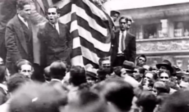 """Multidão saqueia lojas de armas, ataca  jornais pró-Getúlio e atira contra a sede da Legião Revolucionária após comício.Cena do filme """"1932: a Guerra Civil"""" (1993), de Eduardo Escorel"""