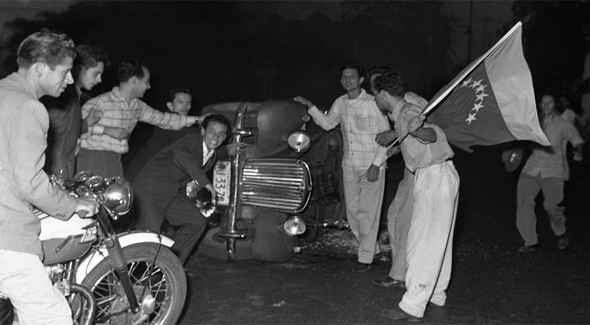 Venezuelanos nas ruas comemoram queda do ditador Jiménez Pérez ao lado de carro tombado. (Foto: Reprodução)