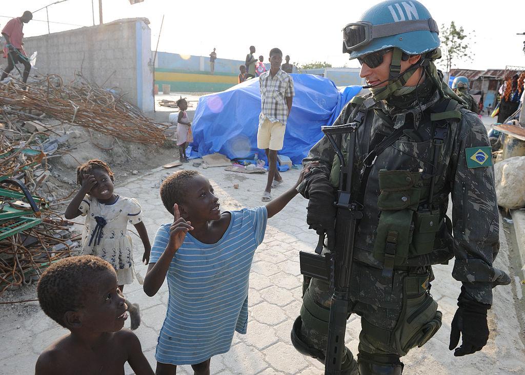 Militar brasileiro caminha com crianças haitianas durante patrulha na Cite Soleil. (Foto: Wikimedia Commons)