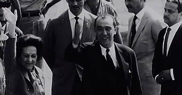 Juscelino e Sarah Kubitschek desembarcam no Rio e são recebidos por dois militares, que entregam ao ex-presidente convocações para depor