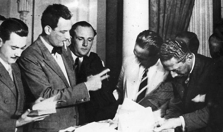 <strong> Filinto M&uuml;ller (com cigarro na boca)</strong> examina documentos apreendidos na casa de Prestes, em mar&ccedil;o de 1936