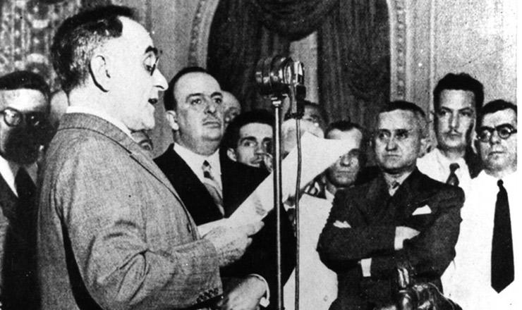<strong> Get&uacute;lio Vargas anuncia </strong> pelo r&aacute;dio o in&iacute;cio novo regime ditatorial. &Agrave; sua direita aparecem o ministro Dutra (de bra&ccedil;os cruzados), Filinto M&uuml;ller (de bigode, atr&aacute;s dele) e o autor da Constitui&ccedil;&atilde;o, Francisco Campos (extrema direita)