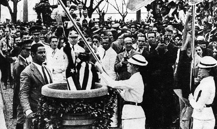 <strong> Bandeira de S&atilde;o Paulo &eacute; depositada </strong> numa pira, onde ser&aacute; incinerada. Abolidas pela nova Constitui&ccedil;&atilde;o,&nbsp;as&nbsp;bandeiras estaduais foram cremadas em cerim&ocirc;nia no dia 2 de dezembro de 1937, na Esplanada do Russell (Rio de Janeiro)&nbsp;