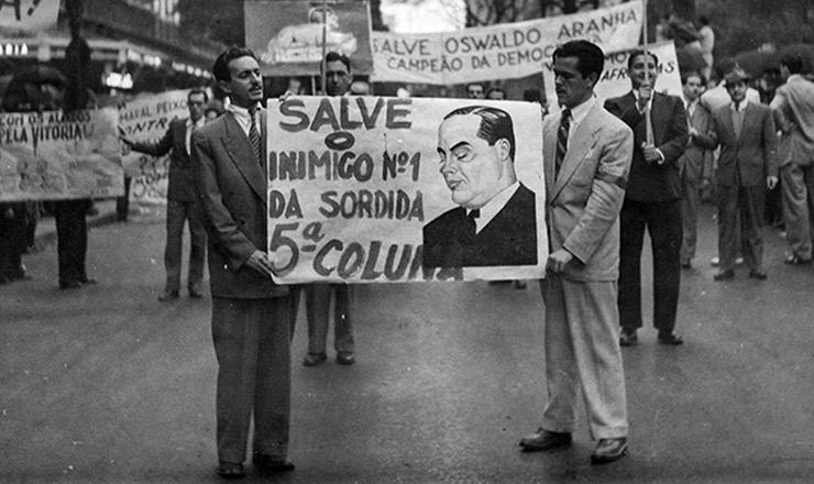 <strong> Estudantes seguram cartaz homenageando</strong> o interventor Amaral Peixoto, na avenida Rio Branco, durante passeata contra o nazifascismo&nbsp;no Rio de Janeiro&nbsp;