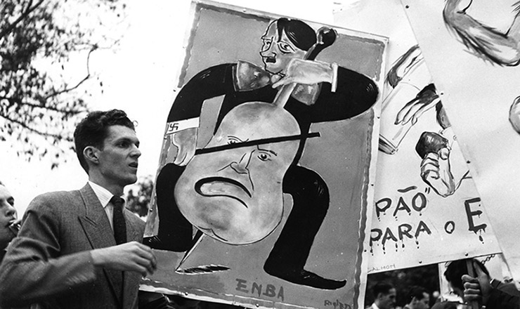<strong> Cartaz satirizando Hitler, </strong> criado na Escola Nacional de Belas-Artes, &eacute; carregado por estante durante manifesta&ccedil;&atilde;o pr&oacute;-Aliados no Rio