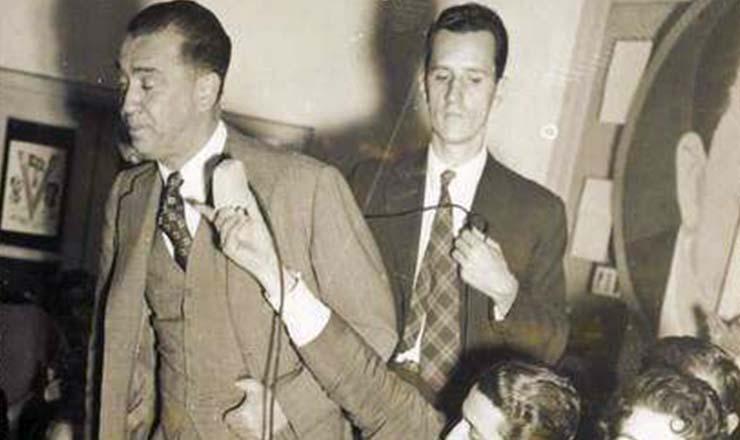 <strong> Juscelino (em p&eacute;) e Jo&atilde;o Goulart </strong> (sentado, batendo palmas) durante evento da campanha à Presid&ecirc;ncia