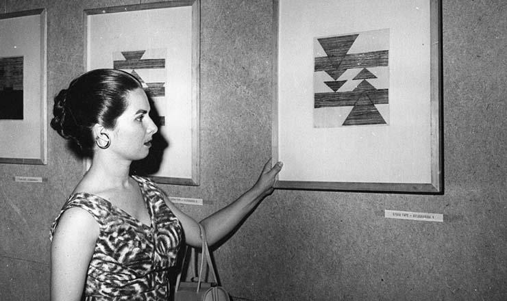 <strong> A artista Lygia Pape posa</strong> ao lado de uma de suas gravuras na Exposi&ccedil;&atilde;o Nacional de Arte Concreta