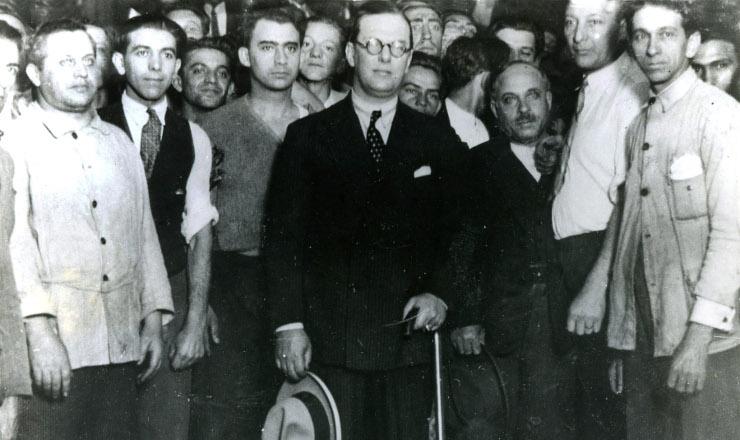 <strong> Lindolfo Collor,</strong> primeiro ministro a ocupar a pasta do Trabalho, cercado de oper&aacute;rios da ind&uacute;stria