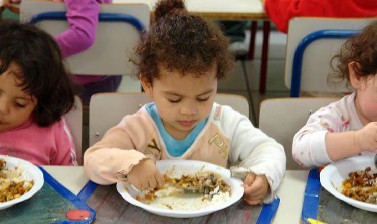 <strong> Crianças se alimentam em cozinha popular: </strong> pol&iacute;ticas de educa&ccedil;&atilde;o e sa&uacute;de elevam o pa&iacute;s ao patamar de desenvolvimento humano elevado