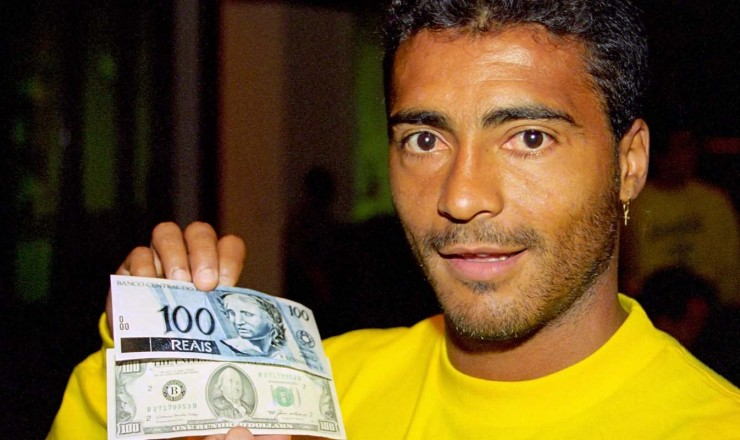 <strong> O jogador Rom&aacute;rio compara </strong> as c&eacute;dulas de R$ 100 e US$ 100; no lan&ccedil;amento da nova moeda, a sele&ccedil;&atilde;o brasileira de futebol disputava a Copa do Mundo nos Estados Unidos  &nbsp;