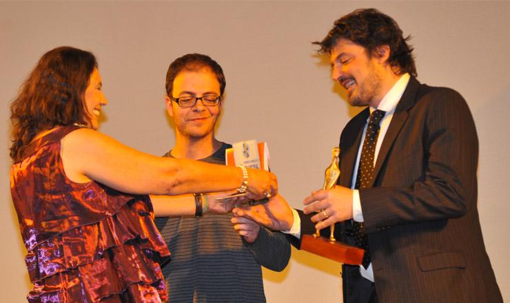 """<strong> Tereza Cruvinelentrega </strong> o prêmio Exibição TV Brasil, na categoria longa-metragem, ao diretor André Ristum (de óculos) e ao produtor Fabiano Gullane, pelo filme""""Meu País"""""""