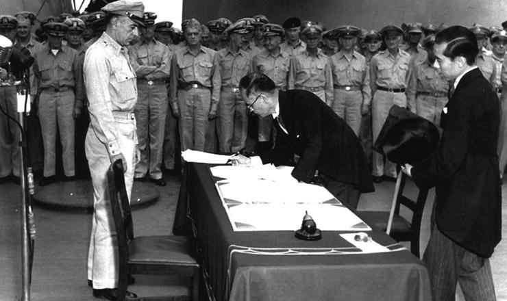 """<strong> O premiê japonês Manoru Shigemitsu </strong> assinao termo de rendição, a bordo do """"USS Missouri"""", na baía de Tóquio, em 2 de setembro de 1945, observado pelo general Douglas MacArthur. Ao fundo, oficiais britânicos e norte-americanos assistem à cerimônia"""