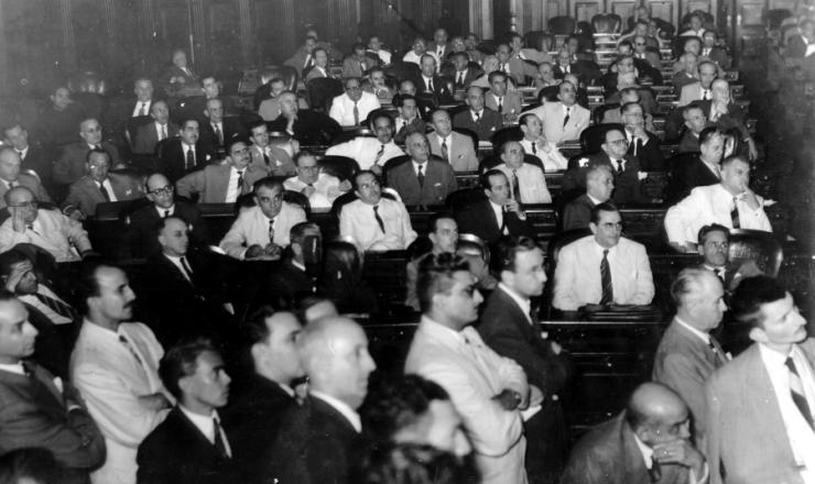 <strong> Vista parcial do plenário </strong> da Assembleia Nacional Constituinte de 1946. Da esquerda para a direita,segunda fila: Gustavo Capanema (2º), José Maria Alckmin (5º), José Francisco Bias Fortes (6º). Na terceira fila: Agamenon Magalhães (7º) e Benedito Valadares (8º)