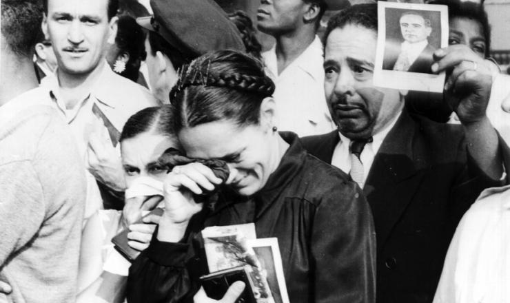 <strong> Populares mostram </strong> com orgulho a foto de Getúlio Vargas durante a passagem do cortejo fúnebre na capital federal