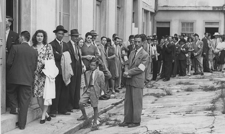 <strong> Fiscal observa fila de eleitores </strong> que aguardam para votar nas elei&ccedil;&otilde;es de 1947, em S&atilde;o Paulo
