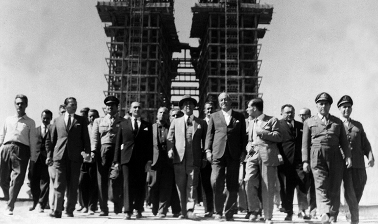 <strong> De chap&eacute;u, o presidente Juscelino caminha</strong> com assessores e correligion&aacute;rios nas obras da futura capital, tendo ao fundo as torres do Congresso Nacional. Bras&iacute;lia, 1959