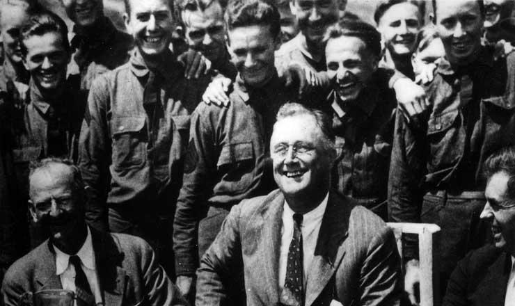 <strong> Franklin Delano&nbsp;Roosevelt, </strong> ao lado de Henry Wallace, secret&aacute;rio nacional da Agricultura,&nbsp;e&nbsp;Robert Fechner, l&iacute;der sindicalista e diretor dos Corpos Civis de Conserva&ccedil;&atilde;o. Roosevelt usou estes &uacute;ltimos como parte do New Deal para dar trabalho a jovens solteiros e desempregados