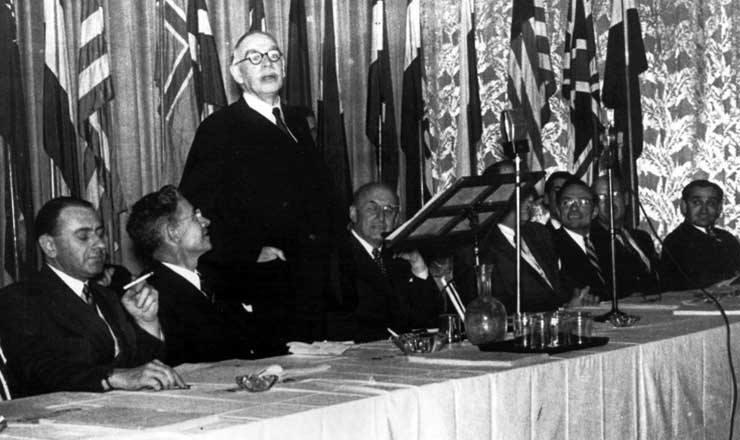 <strong> John Maynard Keynes, autor da proposta brit&acirc;nica, discursa </strong> em Bretton Woods ao lado de Harry Dexter White (&agrave; sua esquerda), autor da proposta norte-americana