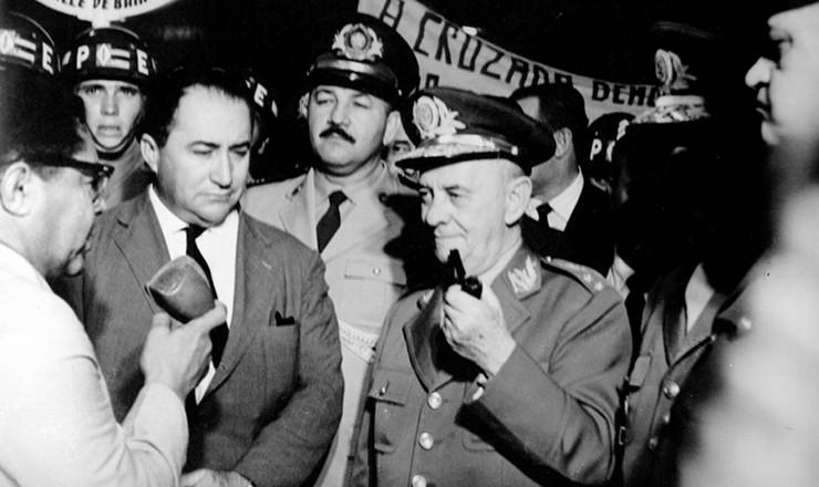 <strong> O militar Ol&iacute;mpio Mour&atilde;o Filho</strong> (de cachimbo) e a Cruzada Democr&aacute;tica, ala que venceu as elei&ccedil;&otilde;es internas do Clube Militar em 1952 e passou a fazer oposi&ccedil;&atilde;o ao governo Vargas, identificado por eles como partid&aacute;rio da ala derrotada