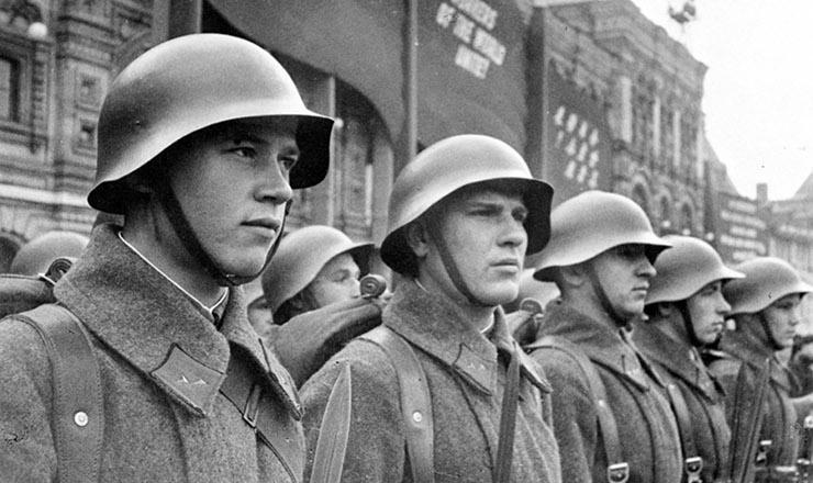 <strong> Soldados do Exército Vermelho mobilizados para a defesa do território sovi&eacute;tico, </strong> em 1941; atr&aacute;s deles, uma faixa exibe, em ingl&ecirc;s, o slogan comunista&nbsp;&quot;Trabalhadores do mundo, uni-vos!&quot;