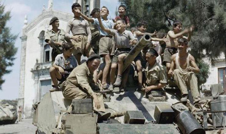 <strong> Garotos locais </strong> sobem em um tanque cruzador brit&acirc;nico Sherman Mk III na localidade de Milo, pr&oacute;ximo a Catania, na Sic&iacute;lia, em agosto de 1943
