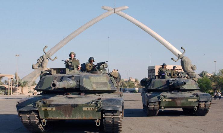 <strong> Militares americanos posam </strong> para foto sob o monumento &quot;M&atilde;os da vit&oacute;ria&quot;, em Bagd&aacute;, capital do Iraque, em novembro de 2003