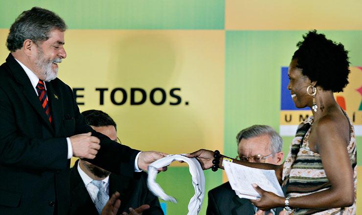 <strong> Solange Aparecida Ferreira de Campos, bolsista do ProUni para curso de gastronomia, entrega </strong> uma faixa da organiza&ccedil;&atilde;o Educafro ao presidente Lula