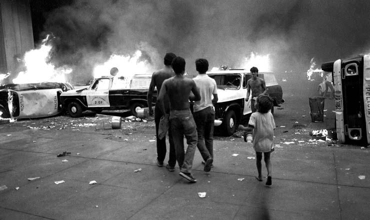 <strong> Viaturas da pol&iacute;cia incendiadas </strong> em protesto em Bras&iacute;lia contra o Plano Cruzado 2; os manifestantes faziam passeata e reagiram &agrave; forte repress&atilde;o policial&nbsp;