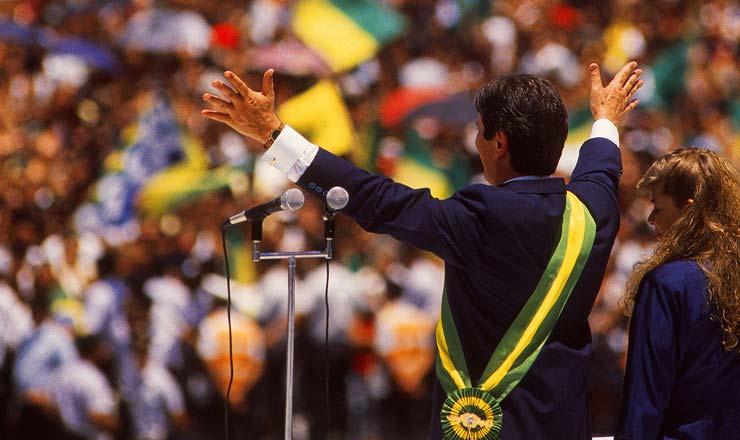 <strong> Fernando Collor cumprimenta</strong> o povo ap&oacute;s tomar posse; no dia seguinte, no primeiro ato de governo, o presidente baixa um pacote econ&ocirc;mico que confisca saldos banc&aacute;rios e da poupan&ccedil;a de todos os brasileiros