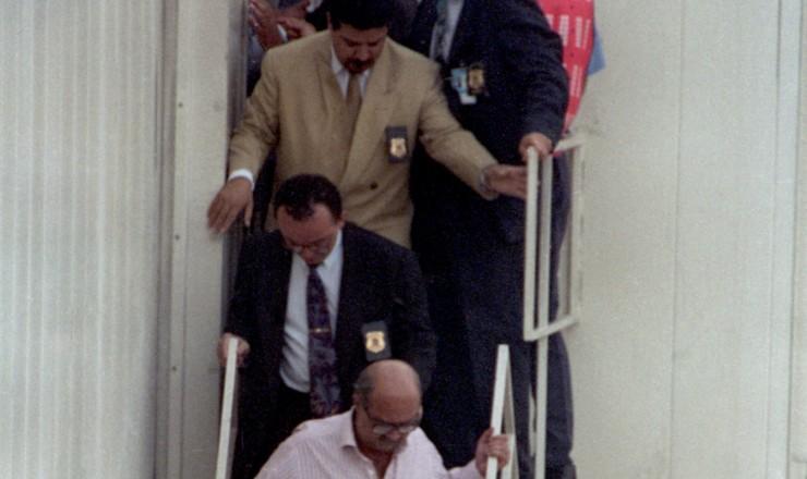 <strong> O empres&aacute;rio Paulo C&eacute;sar Farias </strong> (de camisa cor de rosa) desembarca&nbsp;em S&atilde;o Paulo acompanhado por agentes da Pol&iacute;cia Federal, vindo da Tail&acirc;ndia