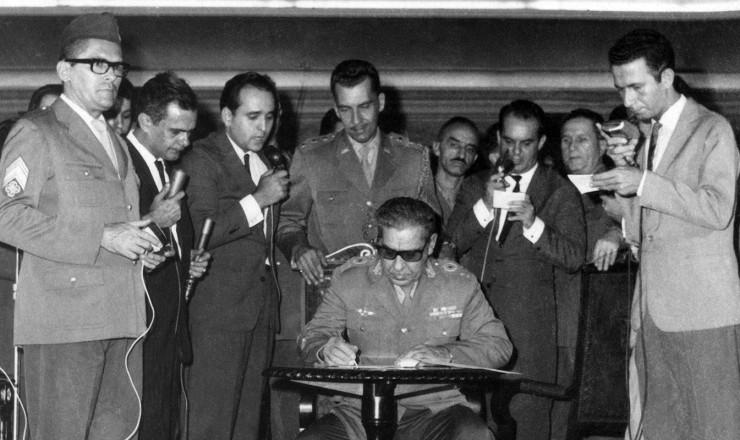 <strong> Arthur da Costa e Silva, </strong> representante do Ex&eacute;rcito no Comando Supremo da Revolu&ccedil;&atilde;o, assina o Ato Institucional da ditadura, primeiro de uma s&eacute;rie de decretos autorit&aacute;rios