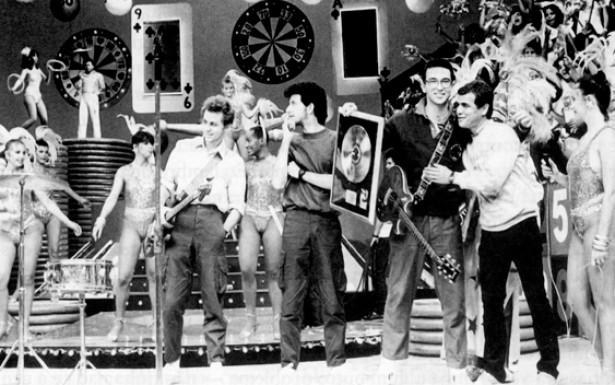 """Após a apresentação no Rock in Rio muitas bandas ganharam projeção nacional, passaram a vender milhares de discos e a fazer aparições constantes na televisão. Na imagem, o grupo Paralamas do Sucesso recebe o disco de ouro no """"Cassino do Chacrinha"""", na época o mais popular programa da televisivo brasileira."""