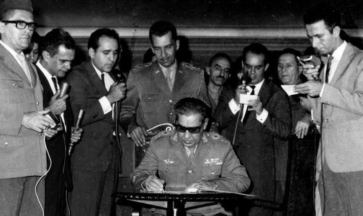 <strong> Costa e Silva assina o AI-1, </strong> o&nbsp;primeiro ato jur&iacute;dico repressivo da ditadura, 9 de abril de 1964